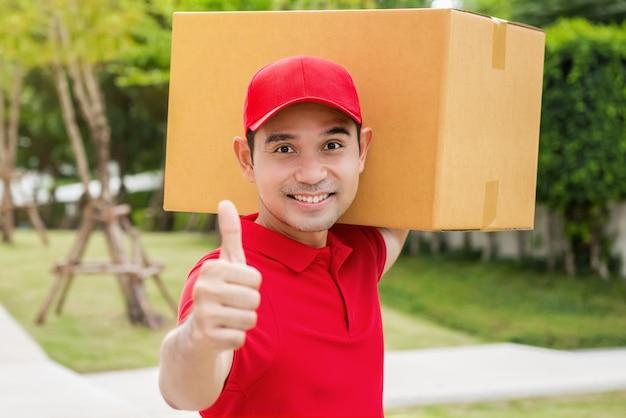 アサイン配達人は親指で箱を抱えています。 Premium写真