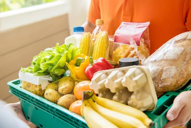 自宅の顧客に食料を配達する食料品店の配達人 Premium写真