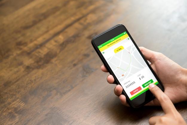 アプリケーションを介してオンラインで予約タクシーを確認するスマートフォンの画面に触れる女性の手 Premium写真