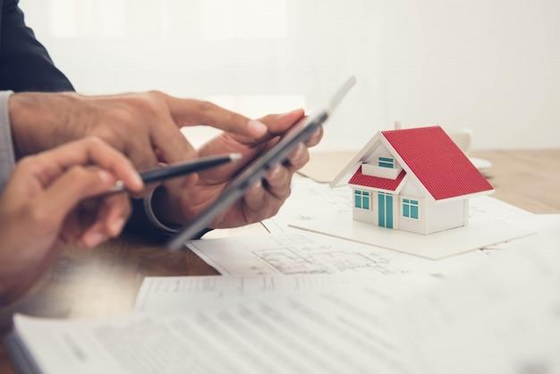 家のモデルの計画を議論する建築家 Premium写真