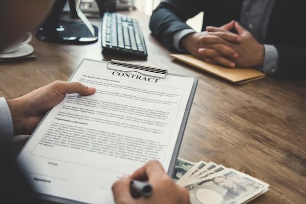テーブルの上のお金、日本円紙幣との契約契約に署名する実業家 Premium写真