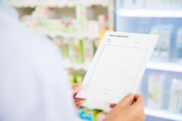 Фармацевт держит рецепт в аптеке или аптеке Premium Фотографии