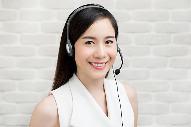 Красивая азиатская коммерсантка нося шлемофон микрофона как агент обслуживания клиента телемаркетинга Premium Фотографии