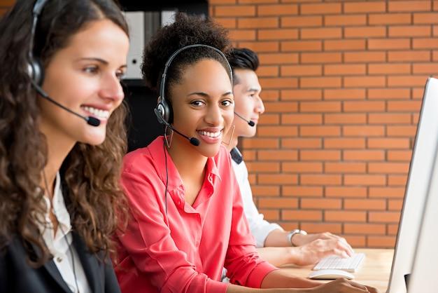 Улыбаясь черный женский телемаркетинг агент обслуживания клиентов, работающих в колл-центр Premium Фотографии