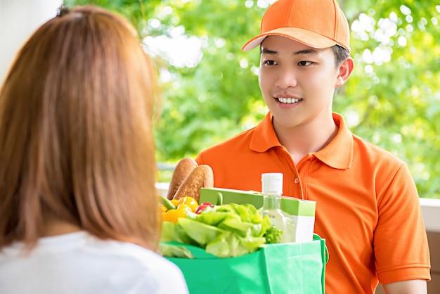 自宅の女性に食べ物を届ける配達人 Premium写真