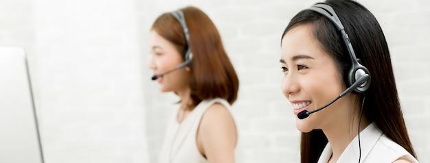 Красивая усмехаясь азиатская команда агента обслуживания клиента телемаркетинга женщины, концепция работы центра телефонного обслуживания Premium Фотографии