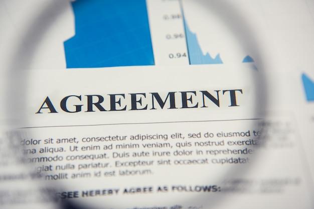 Соглашение документ, глядя через увеличительное стекло Premium Фотографии