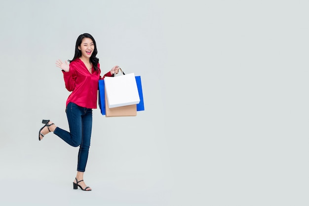 買い物袋と興奮して若いアジアの女の子の笑顔 Premium写真