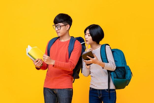 Азиатские студенты мужского и женского пола, глядя на книгу Premium Фотографии