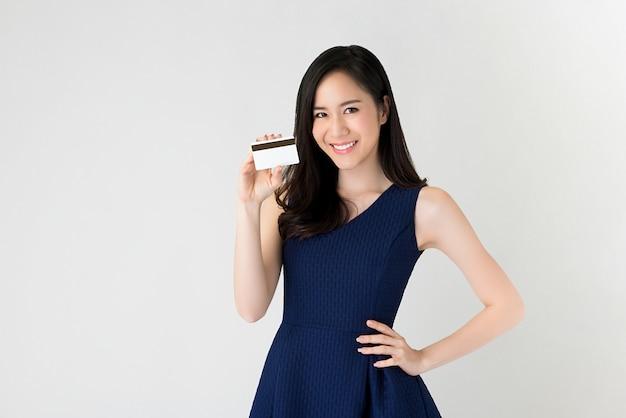 クレジットカードを手に示す美しいアジアの女性 Premium写真