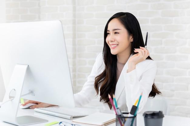 オフィスのコンピューターを使用して美しい働く女性 Premium写真