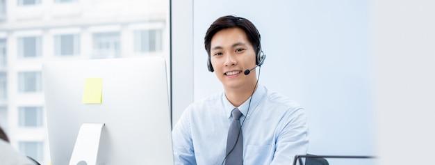 Агент телемаркетинга азиатского человека в офисе центра телефонного обслуживания Premium Фотографии