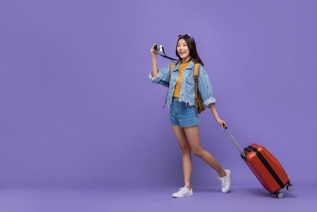 カメラと荷物を持つアジアの観光客の女性の笑みを浮かべてください。 Premium写真