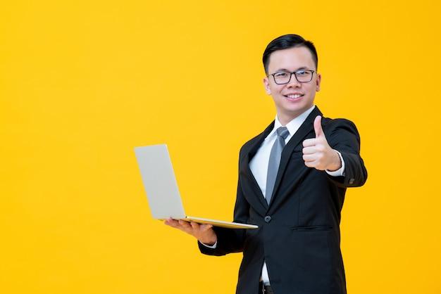 アジア系のビジネスマンのラップトップコンピューターを運ぶと親指をあきらめる Premium写真