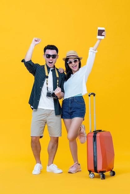 荷物を両手を上げて叫んで興奮したアジアカップル観光客 Premium写真