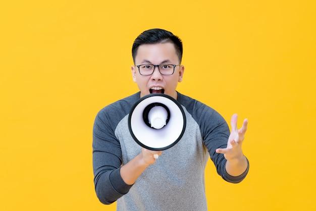 メガホンに叫んで怒っているアジア人 Premium写真