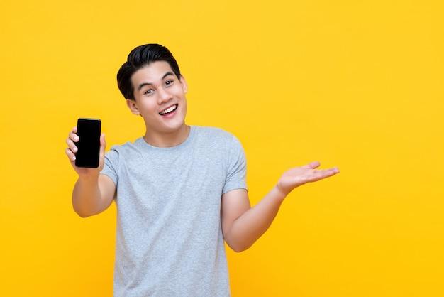 別の手を開いて携帯電話を示す幸せな笑みを浮かべて若いアジア人 Premium写真