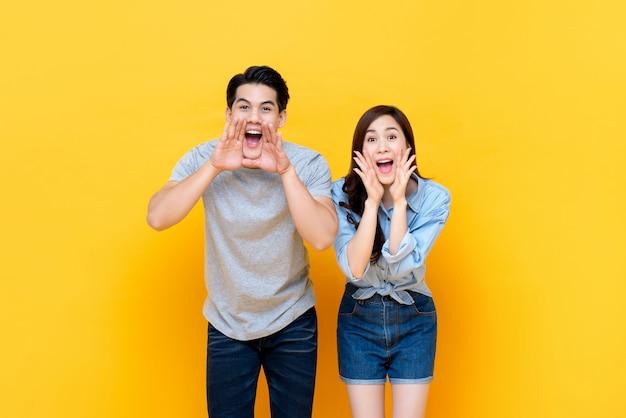 Молодые милые азиатские пары кричали с руки чашку вокруг рта Premium Фотографии