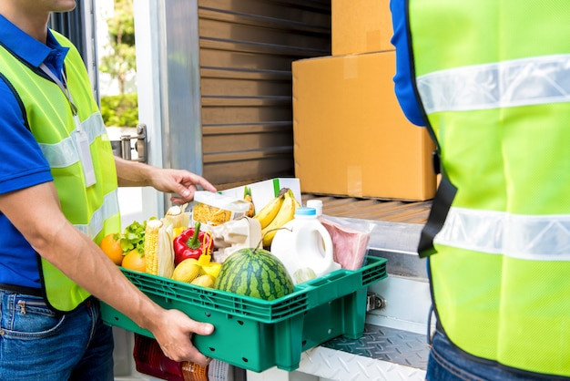 配達する車から取り出す前に食べ物をチェックする配達人 Premium写真