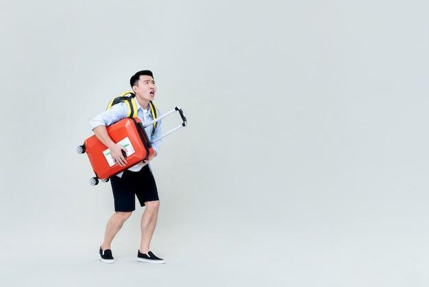Шокирован молодой азиатский турист человек с багажом, глядя вверх Premium Фотографии