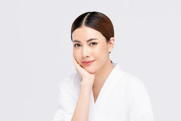 Юношеская сияющая милая азиатская женщина с рукой касаясь лицу Premium Фотографии