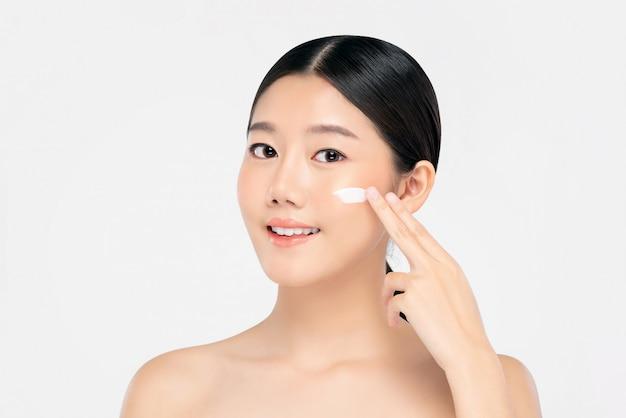 Молодая красивая азиатская женщина, применяя крем для лица Premium Фотографии
