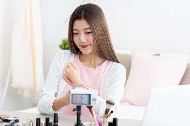 Молодая привлекательная азиатская губная помада испытания красоты женщины на задней части ее руки перед камерой Premium Фотографии