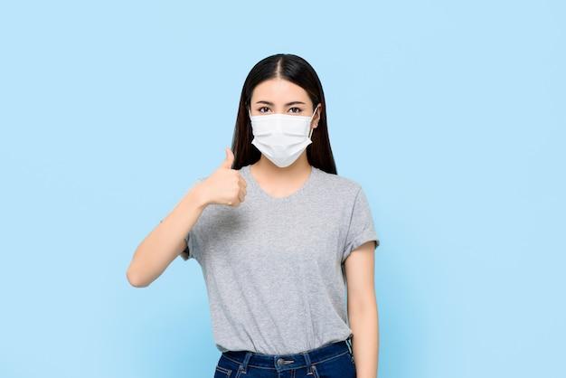 コロナウイルスと水色の壁に分離された親指をあきらめてアレルギーを保護するフェイスマスクを着ている若いアジア女性 Premium写真