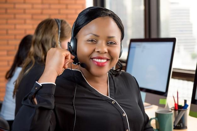 コールセンターで働く笑顔の美しい黒人のビジネスマン Premium写真