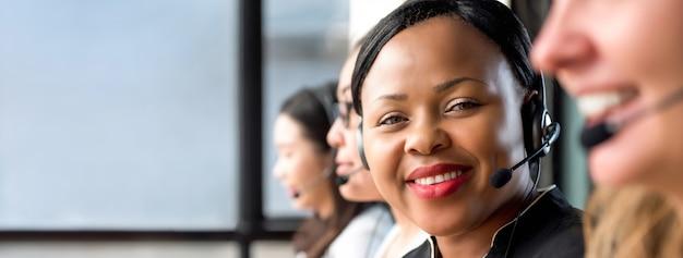 コールセンターで働くマイクヘッドセットを着ている親しみやすい黒人の女性 Premium写真