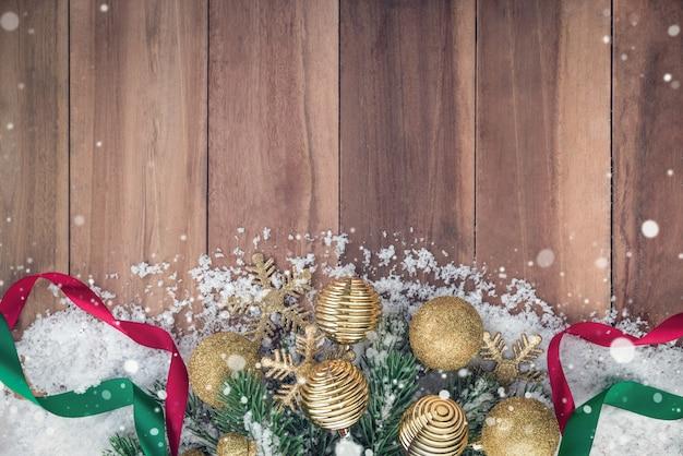木の背景に雪を持つクリスマスの装飾品 Premium写真