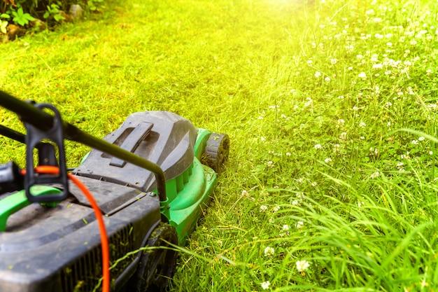 裏庭の芝刈り機で緑の草を刈る男。ガーデニングの国のライフスタイルの背景。 Premium写真