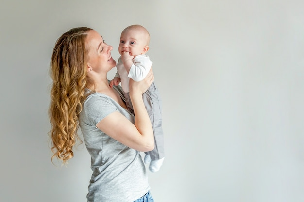 彼女の生まれたばかりの子供を持つ若い母親。女性と幼児の少年はリラックスして遊ぶ Premium写真