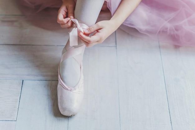 バレリーナの手は足にトウシューズを履く Premium写真