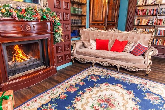 古典的なクリスマスの新年は、暖炉のあるインテリアルームのホームライブラリを装飾しました。 Premium写真