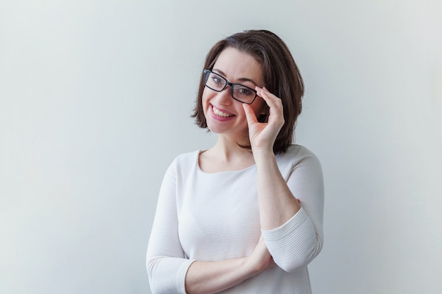 笑っている美しい幸せな女の子。白で隔離の眼鏡の美しさシンプルな肖像若い笑顔ブルネットの女性 Premium写真