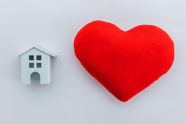白で隔離赤いハートとミニチュアの白いおもちゃの家でシンプルなデザイン Premium写真