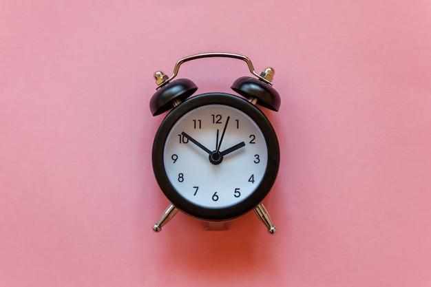 ピンクのパステル調の背景に分離されたビンテージの目覚まし時計 Premium写真