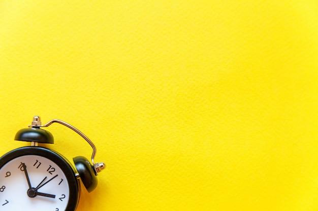 黄色の背景に分離されたビンテージの目覚まし時計 Premium写真