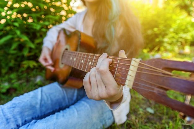 公園または庭でアコースティックギターを弾く女性の手のクローズアップ Premium写真