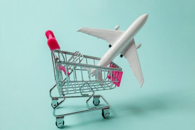 おもちゃの飛行機と青の背景にショッピングプッシュカート Premium写真