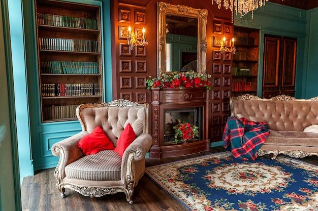 ホームライブラリの豪華なクラシックなインテリア。本棚、本、アームチェア、ソファ、暖炉のある応接間。 Premium写真