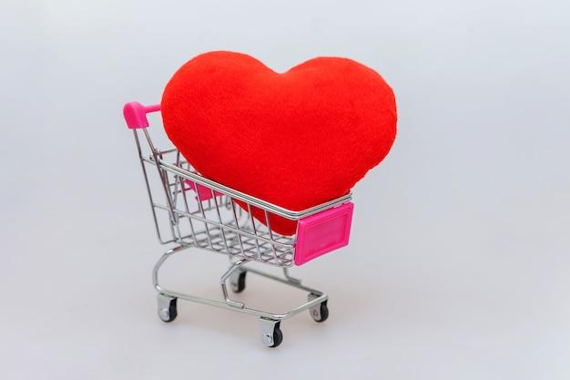 ショッピング、白で隔離される心のための小さなスーパー食料品のプッシュカート Premium写真