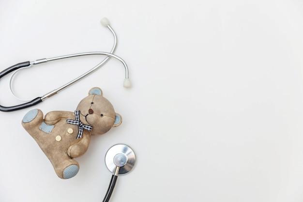 Просто минимальный медведь игрушки дизайна и стетоскоп оборудования медицины изолированные на белой предпосылке. концепция здравоохранения детей доктор. символ педиатра плоская планировка, вид сверху копией пространства Premium Фотографии