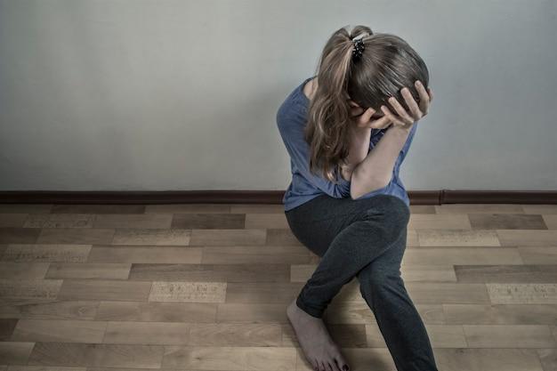 うつ病の女性が床に座っている。悲しい、絶望的な、抑圧された女の子。 Premium写真