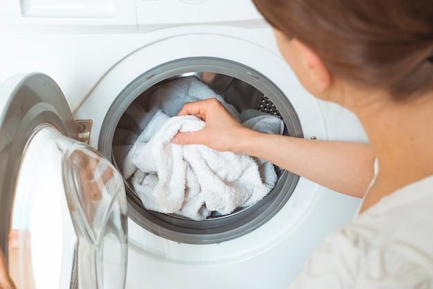 女性が洗濯機用の汚れた服を積みます。 Premium写真