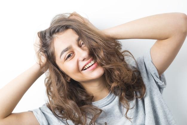Ся индийская девушка на белой предпосылке. молодая счастливая женщина брюнетка. Premium Фотографии