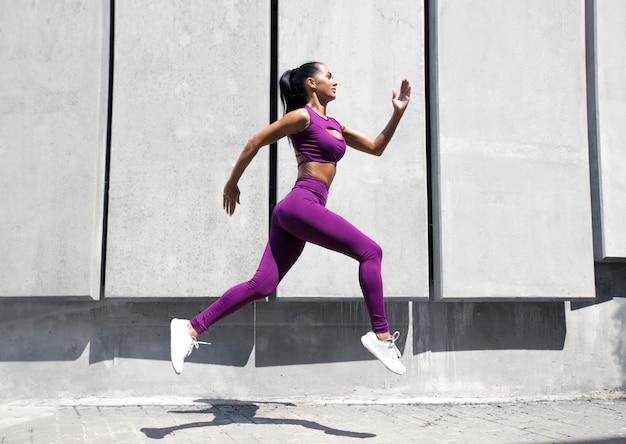 動的な動きでスポーティな女性ランナー。フィット感と健康的な女の子が路上でトレーニング。フィットネス女性。 Premium写真