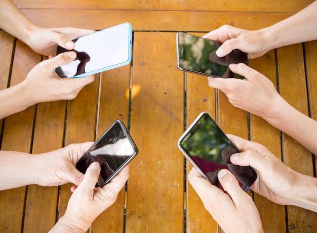 スマートフォンと一緒に楽しんでいる友人のグループ。手でクローズアップの携帯電話。 Premium写真