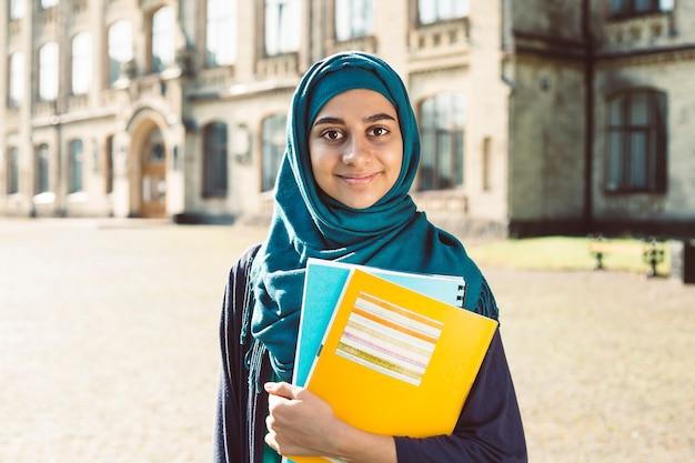 大学の近くに立って本を持って笑顔のイスラム教徒の若い女子学生。ヒジャーブで幸せなアラビアの女の子。トレーニングのアジア女性。 Premium写真